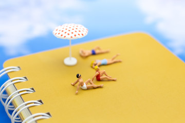Miniature people: Travelers lie sunbathe on the book brown and blue ocean. Image use for vacation, summer, relax time concept.