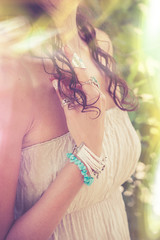 closeup of young woman hand with  lot of boho style jewrly, rings and bracelets outdoor light leak