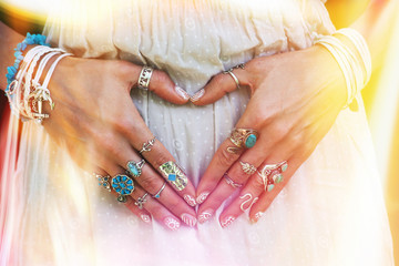 closeup of young woman hands in heart shape with lot of boho style jewrly, rings and bracelets outdoor light leak