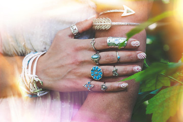 closeup of young woman hand and arm with lot of boho style jewrly, rings and bracelets outdoor light leak
