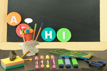 Back to school. Blackboard with the letters A B H I and school equipment on black slate.