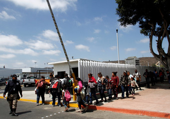 Migrant families walk to enter the United States border and customs facility to apply for asylum, in Tijuana