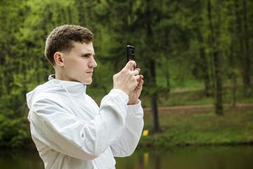 Парень в парке фотографирует на телефон