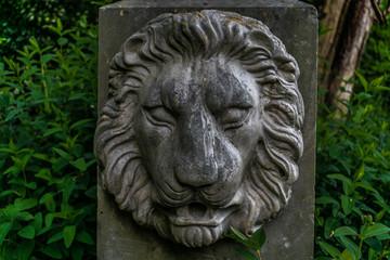 Pietra miliare con effige di leone in un giardino pubblico italiano