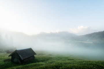 Hut in the mountain with fog and sunrise