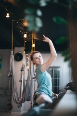 Girl ballerina, the dancer kneads in training. Instructor for stretching in hammocks, yoga.