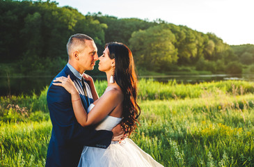 bride and groom on their wedding day, nature walks, kiss and hugs, sunset