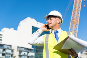 Man architector outdoor at construction area having mobile conversation