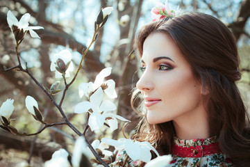 Beautiful young women with fresh look and stylish make-up against the background of cherry blossoms
