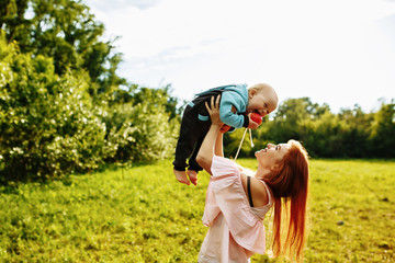 a red-haired woman holds her young son in her arms at sunset in a green Park. They eat an Apple together.