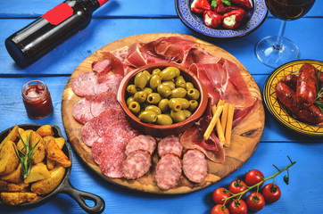 Spanish tapas on wooden table, top view
