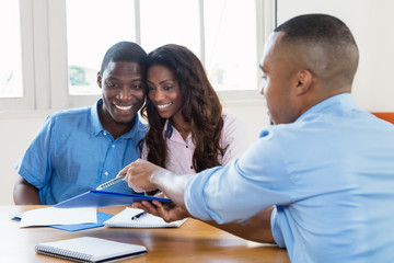 Laughing african american couple with contract of agent