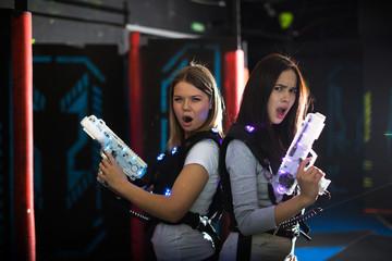 Girls back to back with laser guns