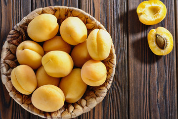 Ripe yellow apricots in bowl on a wooden table