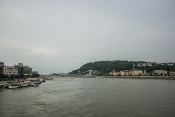 Budapest waterfront in gray rainy day time with river and ships