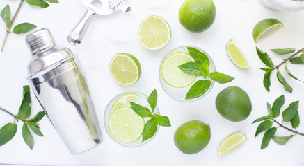 Refreshing mint alcohol cocktail mojito with rum and lime, cold drink or beverage with ice, juice, soda water, shaker and bar utensils on white table. Top view. Flat lay.
