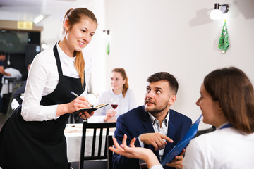 Welcoming female waiter is taking order from couple in restaurante