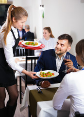 Woman waiter is giving dish to client in restaurante