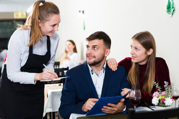 Couple is giving order to female waiter in luxury restaurante
