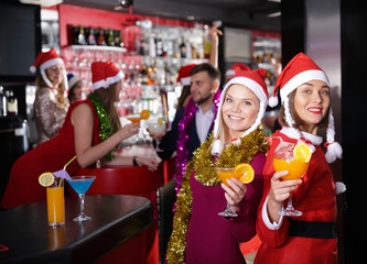 Female colleagues enjoying corporate new year party in bar