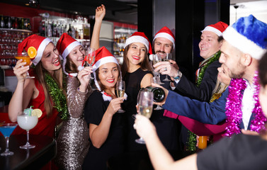Young people in Santa hats celebrating at nightclub