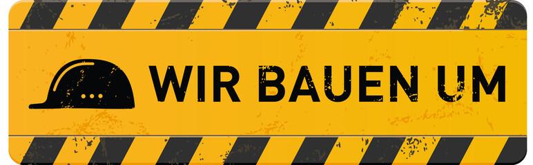 gelbes Schild Wir bauenn um mit Helm-Icon