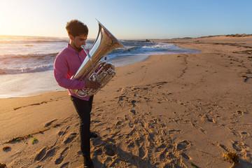 Musician play Tuba on the ocean coast.