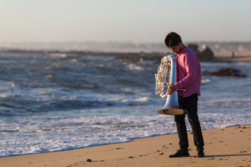 Musician with Tuba on the ocean coast.