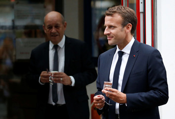 French President Emmanuel Macron holds a dessert during a visit to the SILL Enterprises milk processing plant in Plouvien