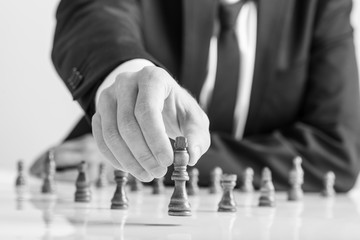 Greyscale image of businessman wearing business suit moving dark King chess piece