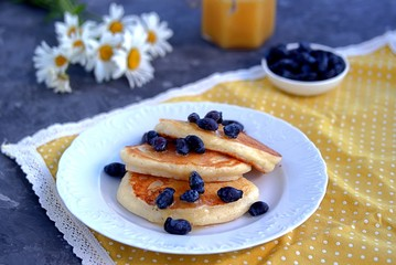 Oatmeal pancakes with honey and berries on a dark gray concrete background