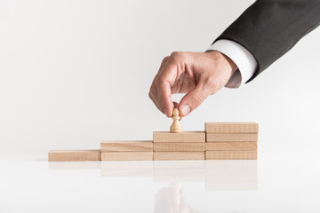 Conceptual image of career management with a businessman placing pawn chess piece