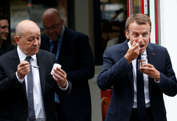 French President Emmanuel Macron and Foreign Affairs Minister Jean-Yves Le Drian hold desserts during a visit to the SILL Enterprises milk processing plant in Plouvien