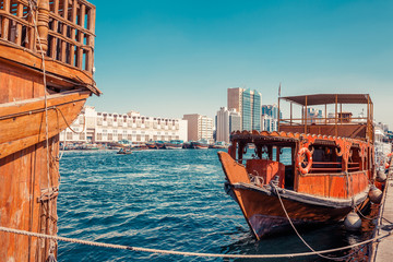 Skyline view of Dubai Creek with traditional boats and piers. Sunny summer day. Famous tourist destination in UAE.