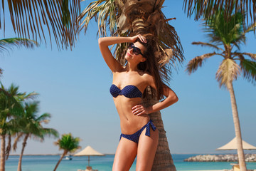 Sexy beautiful woman relaxing and sunbathing in bikini on sea background and palm tree. Panoramic view from Al Mamzar beach in Dubai, UAE. United Arab Emirates famous tourist destination.