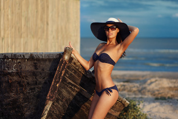 Portrait of sexy beautiful tanned woman posing in fashion swimwear bikini, hat and sunglasses at the sea coast. Exotic country travel and rest concept. Slim figure and sexy body.