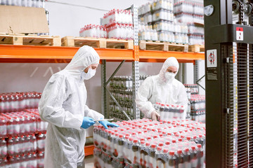 Sports nutrition production employees in protective clothing unloading packs of plastic bottles in warehouse.
