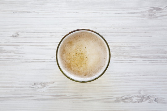 Top view glass of light beer over white wooden background.