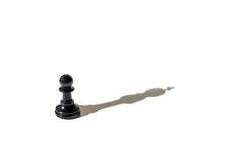 Chess pawn casting the shadow of the king.