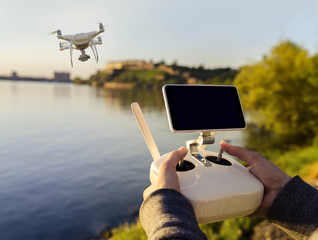 Closeup man hand operating drone by the river