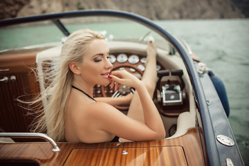 Beautiful young blonde girl is wearing sexy fashion swimsuit doing summer trip on a yacht
