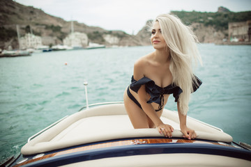 Beautiful young blonde girl is wearing black swimsuit doing summer trip on a yacht