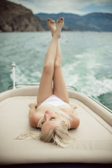 Beautiful young sexy blonde woman is wearing white swimsuit doing summer trip on a yacht