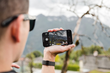Man making photo of nature landscape on smartphone