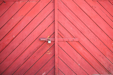 The gate is made of wooden boards painted red. The gate doors are closed with a metal padlock. Red background of wooden planks.