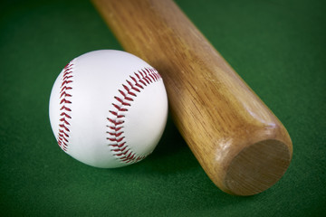 White Baseball ball and wooden bat isolated on green felt background
