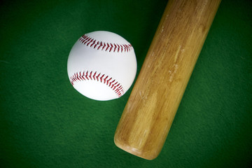 White Baseball ball and wooden bit isolated on green felt background