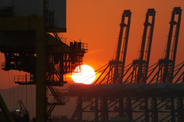 Industrial machinery silhouetted against the rising sun. The sky is orange, and the sun is a white sphere.