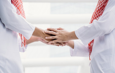 Two Arab shaking hands to greet.