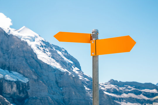 Arrow direction sign with snowy mountain
